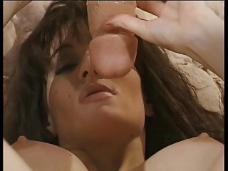 Horny brunette licks and takes dildo in bed alone