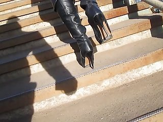 Girl in black leather boots and tan stockings going upstairs