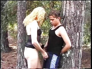 Skanky blonde tranny sucks young guys dick in the woods