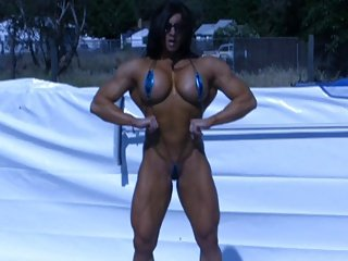 Female bodybuilder posing at poolside