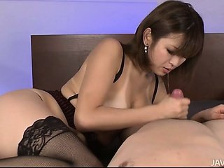 Sexy tanned Mai Kuroki in bed playing with a randy guys dick making him cum