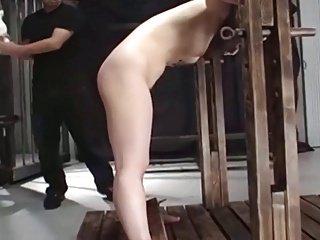 Girl in stockade. spanking