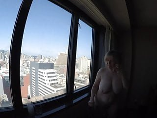 Busty GILF naked overlooking city